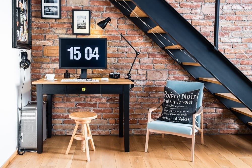 Industrial brick wall under stairs turned into an office space with desk