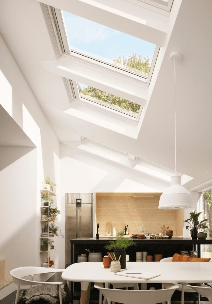 Side single storey home extension featuring roof windows and a dining table