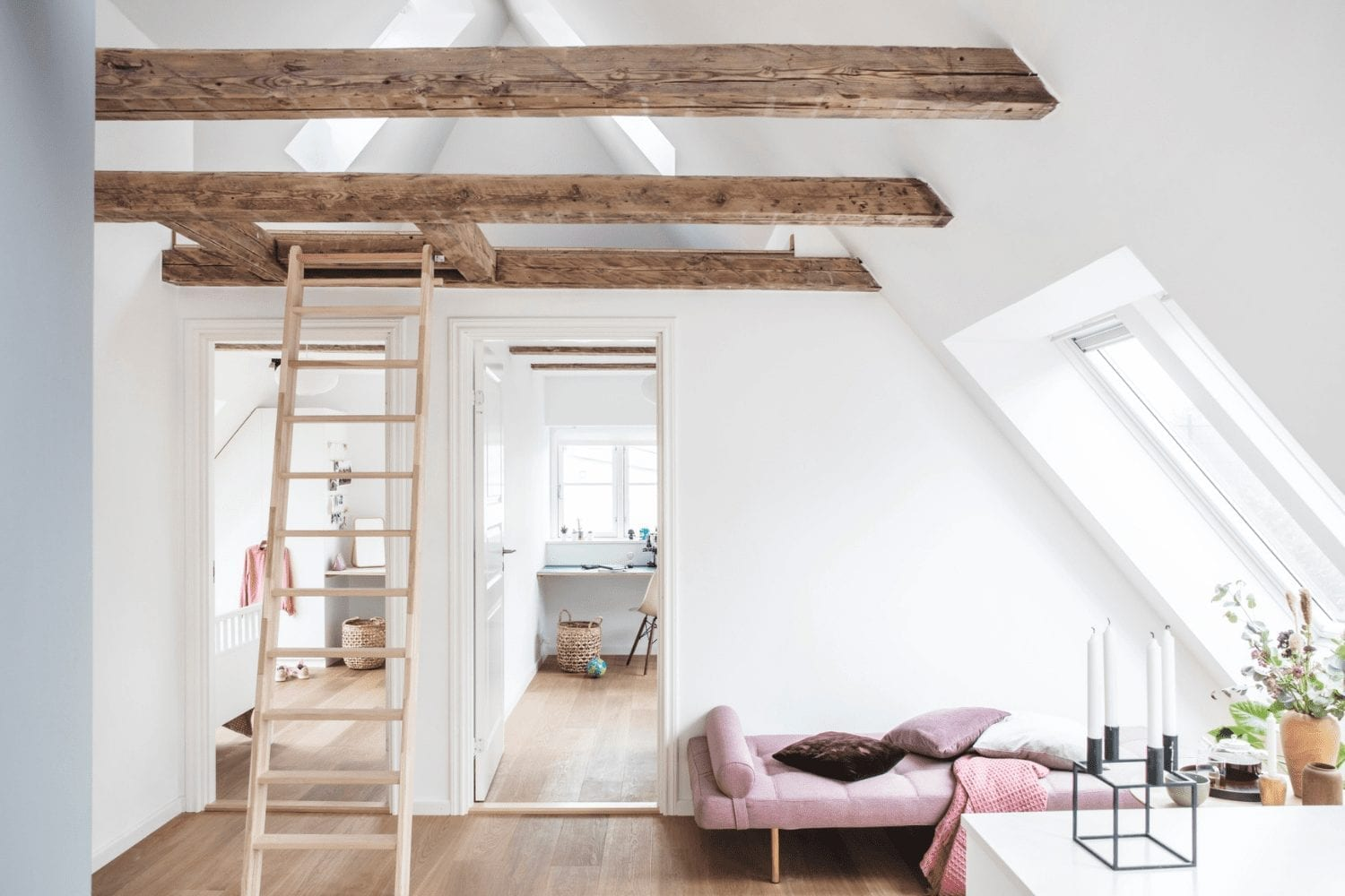 A beautiful white loft conversion with roof windows, a step ladder and two doorways to other rooms