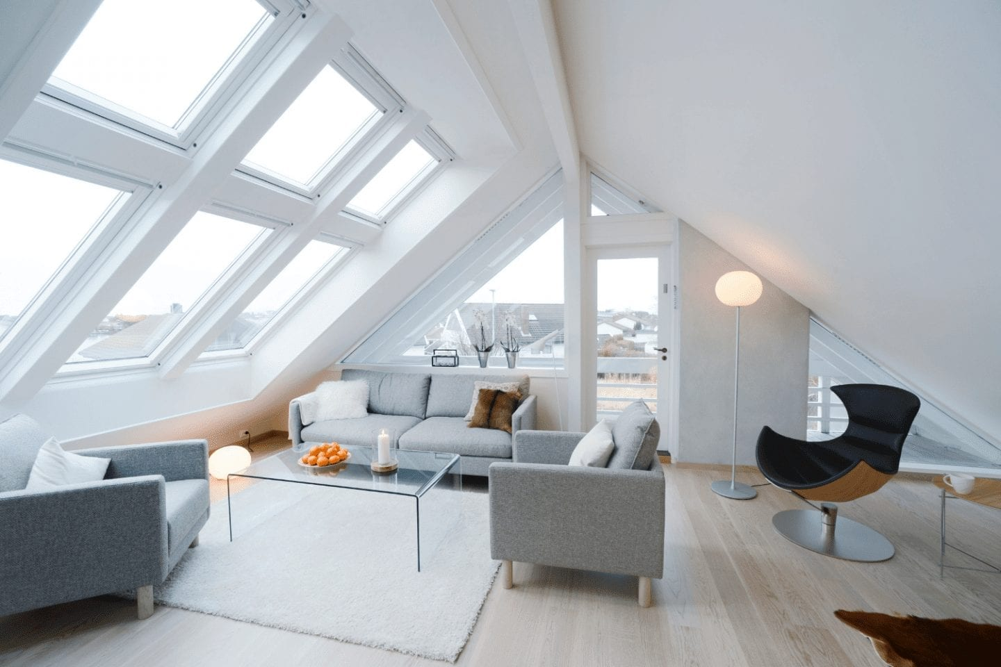 White decorated loft conversion turned into a sitting room with lots of light and windows