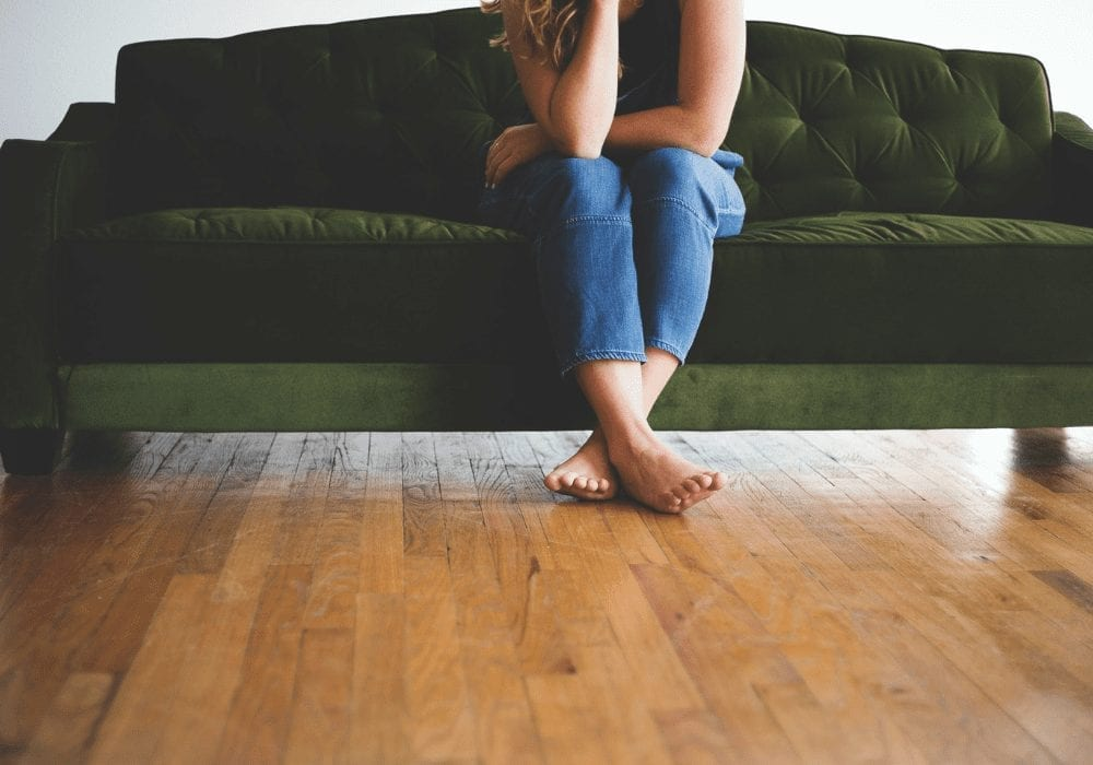wooden floor with green sofa and girls legs