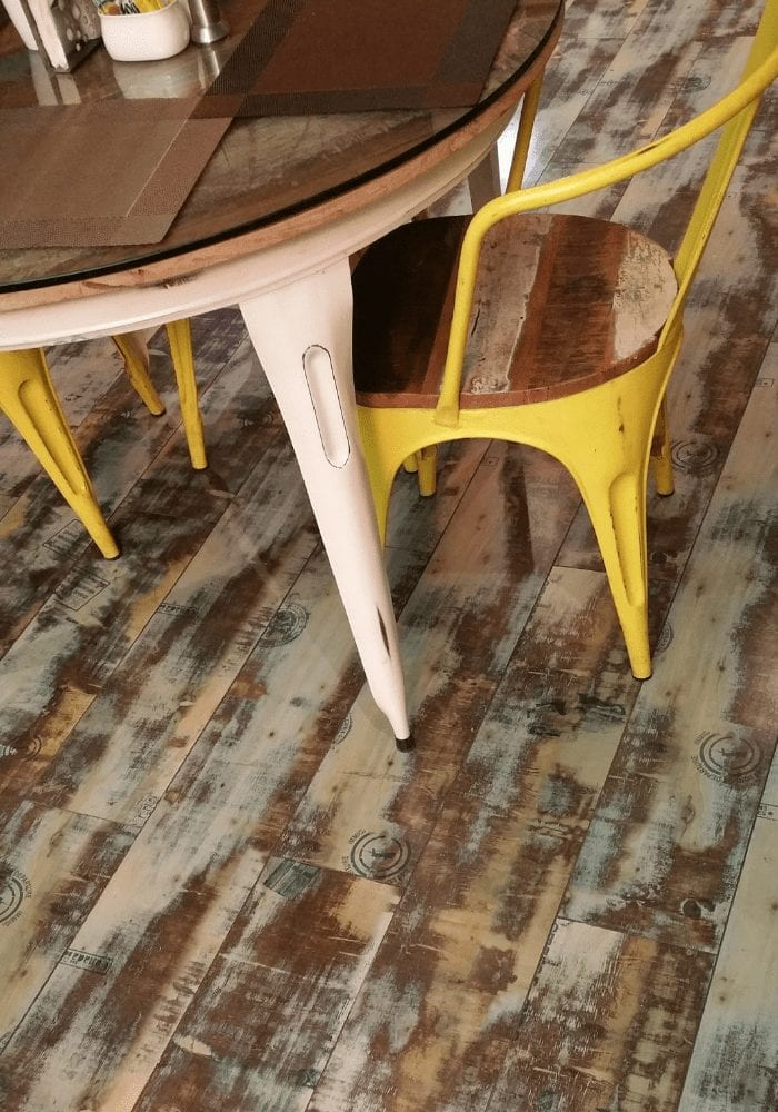 rustic wooden floor with round dining table and yellow metal chairs