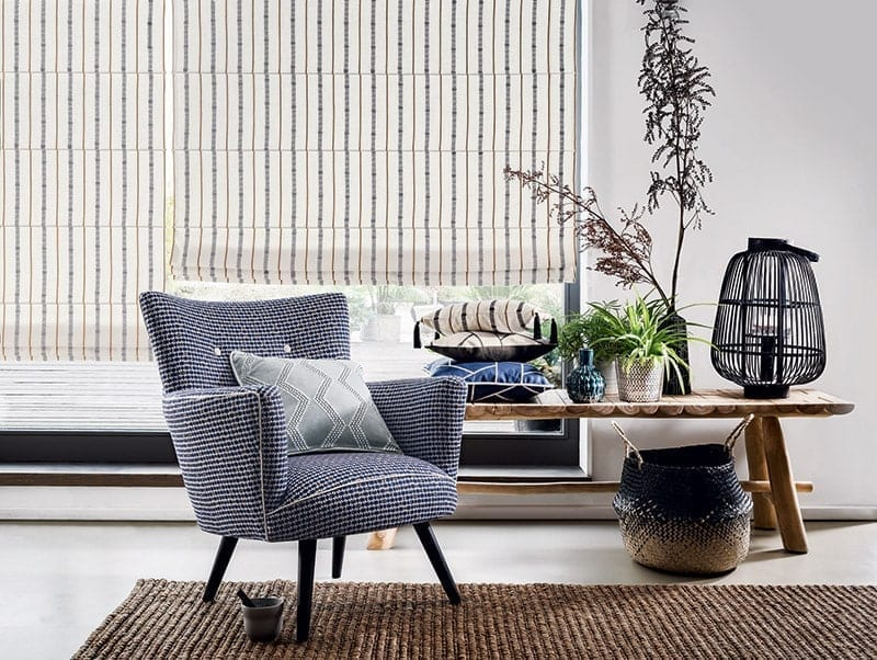 pale made to measure blinds at a large window with blue chair and small table