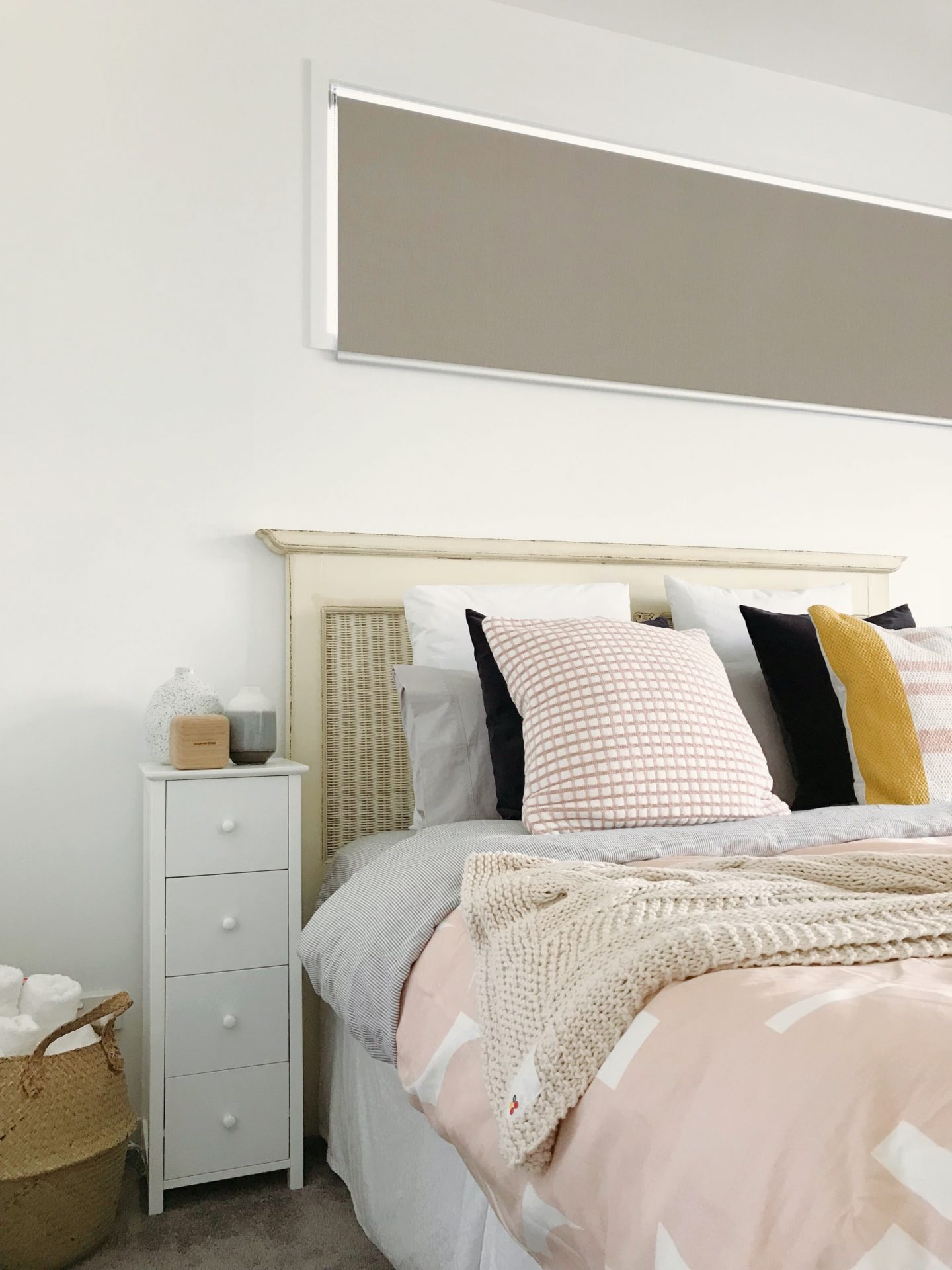 comfortable bed with peach sheets, pillow and throw next to a tall bedside table in a white room
