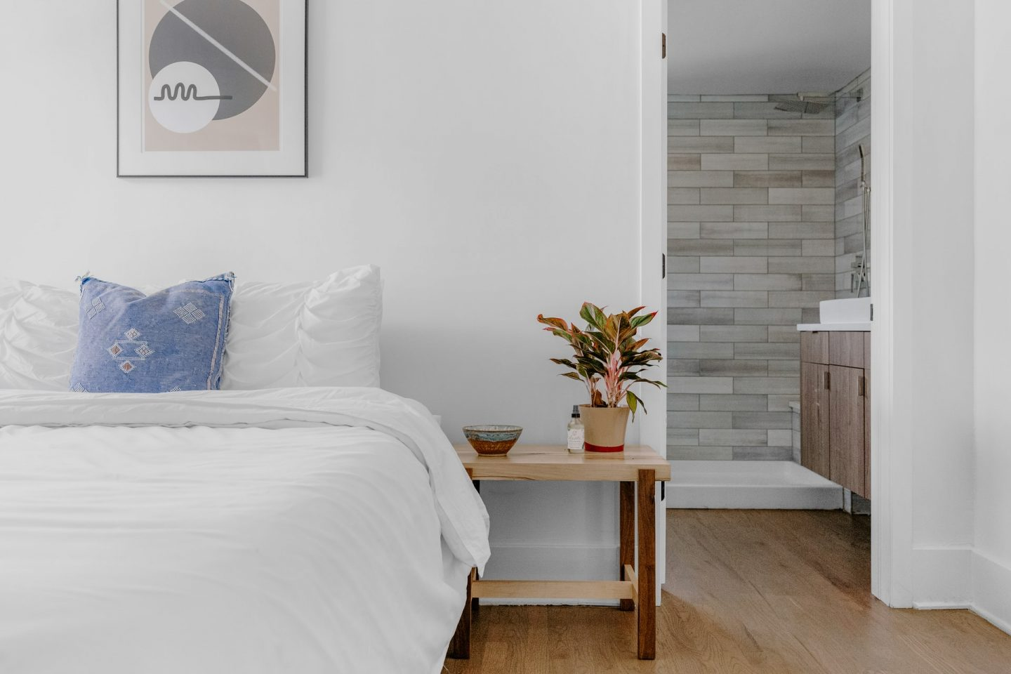 lifestyle shot of a white bed, wooden floor and white walls leading into a contemporary looking en-suite bathroom