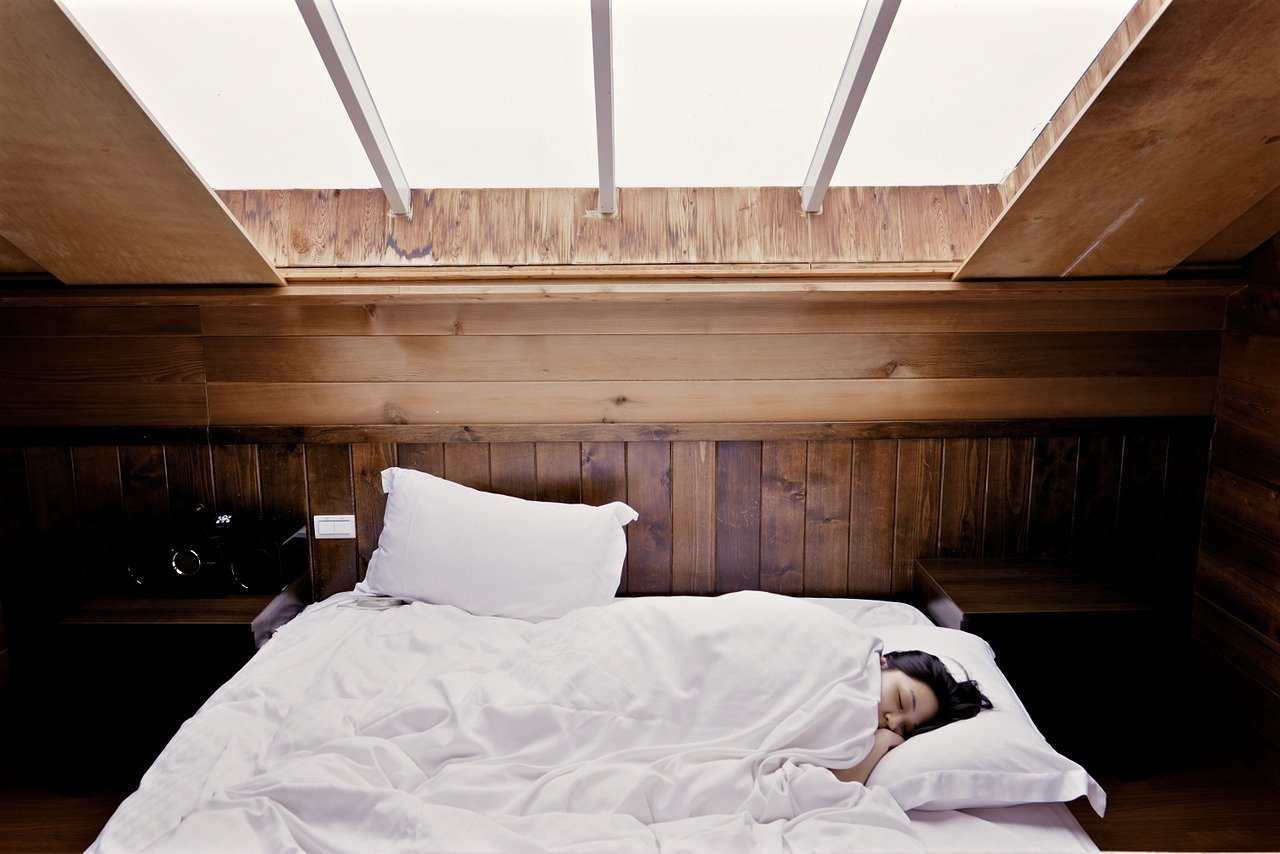 person sleeping in a bed with white sheets