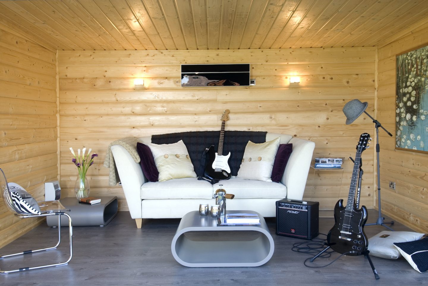 Great garden room idea of a music room showing white sofa and guitars