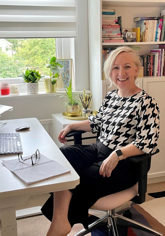 Jen is sat in a new desk chair at a home office desk, in a black and white check top and black trousers. She is smiling